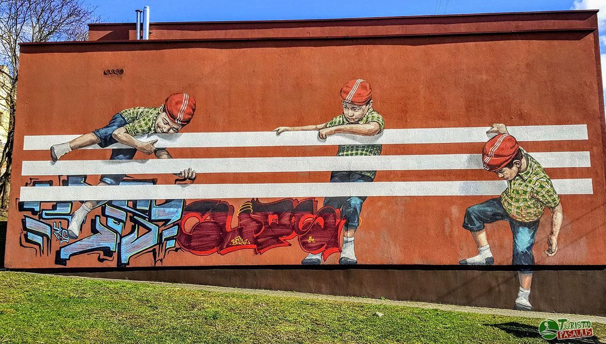 Graffiti Berniukas lipa per tvorą